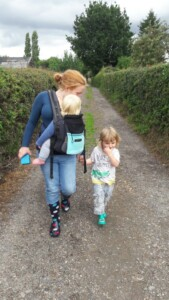 A Mum front carrying her large 1 year old weighing 15kg whilst holding preschooler's hand