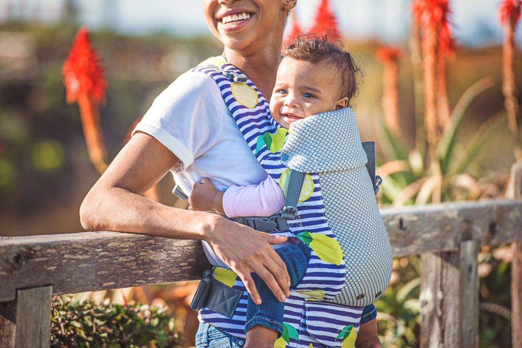 A black woman carrying her baby in a buckle carrier with a lemon design. She is leaning against a fence