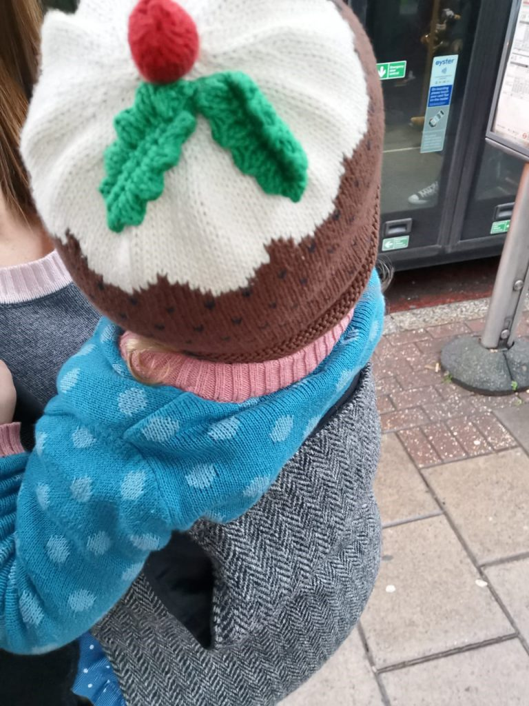 Baby in a Tweed Integra back carry with a christmas pudding hat