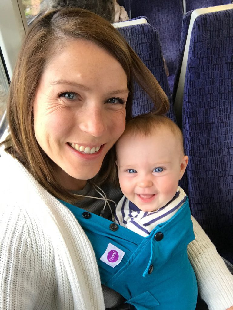 A smiling woman with a young baby in a teal Izmi baby carrier on a train