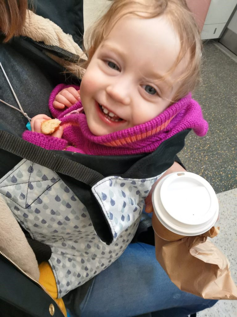A smiling toddler in an Integra Baby Carrier with a raindrops print