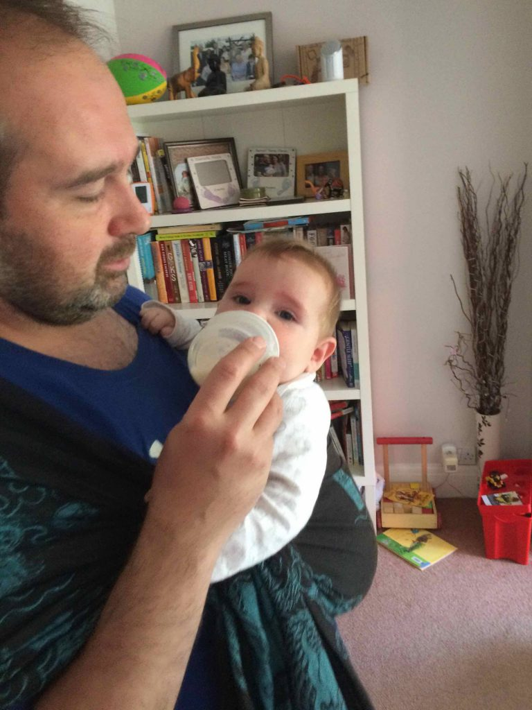 A white man carrying a baby in a blue and black oscha ring sling whilst bottle feeding her