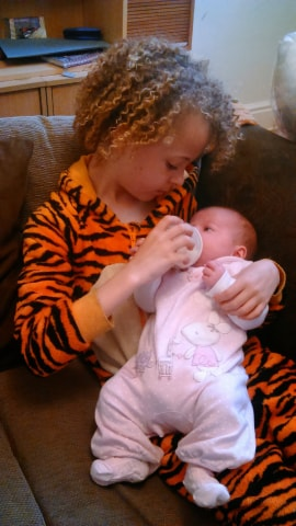 Young curly haired child bottle feeding a baby