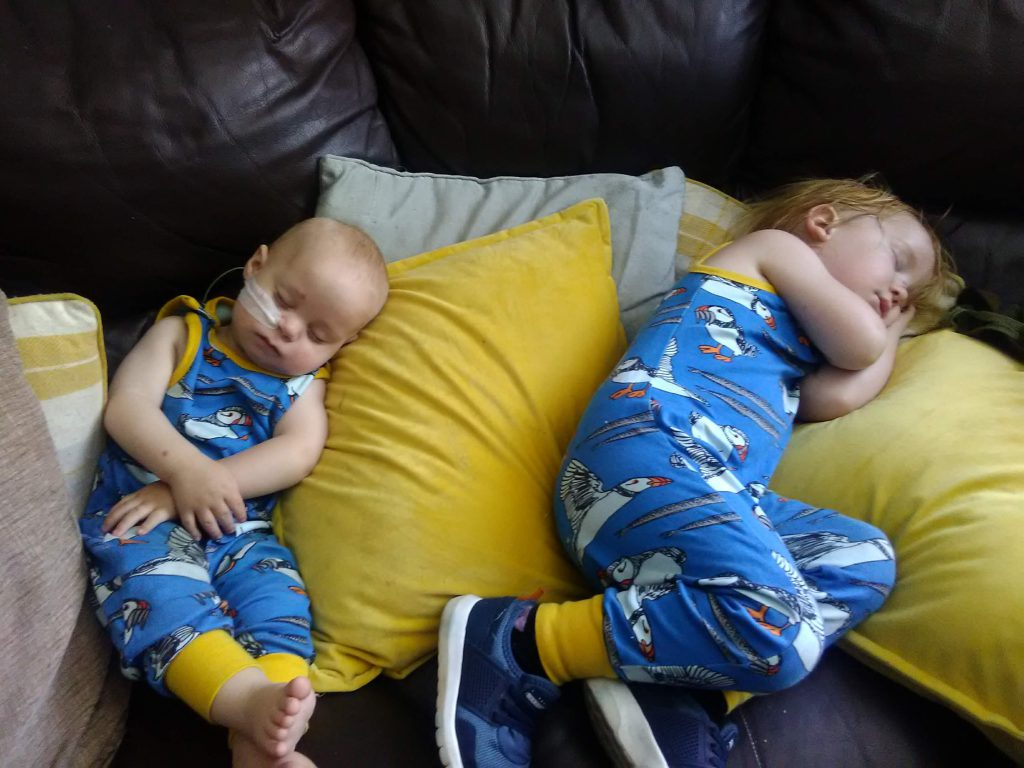 Baby and a toddler in matching blue printed dungarees having a nap on some yellow and white cushions