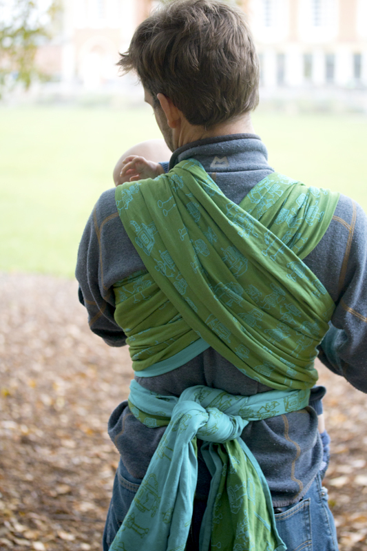 sally sycha slings woven wraps Retrobots Spring Sky back of a man wearing his child in a front wrap cross carry in the blue and green robot designed sling available to hire from It's A Sling Thing online sling library on our Try Before You Buy Scheme
