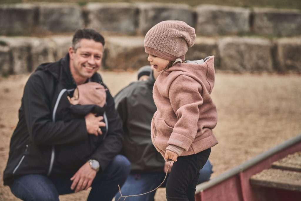 A family sit at the beach watching their toddler in a pink hoody. The man is wearing a black babywearing coat with a baby in a pink hat on his front. The other adult is wearing a grey babywearing coat with a baby on their back in a grey hat.