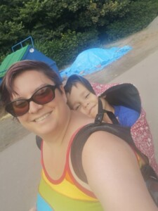 A white woman with short hair and a rainbow vest top back carrying a 4 year old white boy in a red Integra baby carrier with a white mushroom pattern