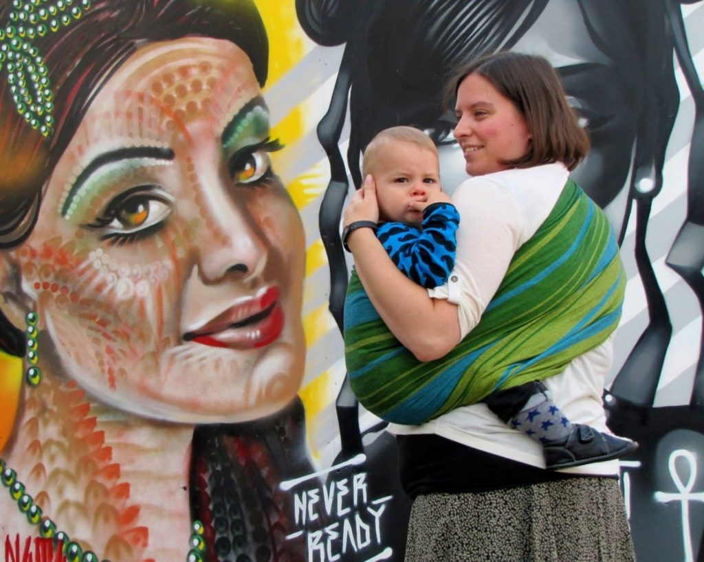 A white woman carrying a toddler in a green ring sling in front of a mural on a wall